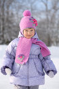 Happy little girl wearing in pink scarf and hat smiles next winter forest Royalty Free Stock Photo
