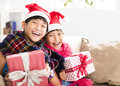 Happy little girls showing christmas gift on  sofa Royalty Free Stock Photo
