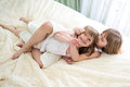 Happy little girls sisters hugging and kissing on bed Stock Photography
