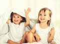 Happy little girls twins sister in bed under the blanket having fun smiling Royalty Free Stock Image