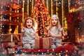 Photo : Happy little girls wearing Christmas pajamas open gift box by a fireplace in a cozy dark living room on Christmas eve. happy and xmas