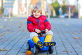 Happy little kid boy driving toy car outdoors Royalty Free Stock Photo