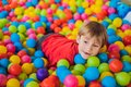 Happy little kid boy playing at colorful plastic balls playground high view. Adorable child having fun indoors Royalty Free Stock Photo