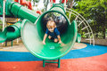 Happy little kid boy playing at colorful playground. Adorable child having fun outdoors Royalty Free Stock Photo