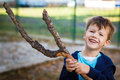 Happy little kid with branch and teeth smile outdoor Royalty Free Stock Photos