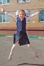 Happy little schoolgirl jumping raising his hands up Stock Images