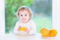 Happy little toddler girl drinking orange juice next to a big window Stock Photography