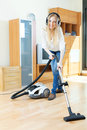 Happy long haired woman with vacuum cleaner in headphones cleaning Royalty Free Stock Photography