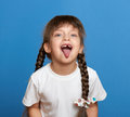 Happy lost tooth girl portrait, studio shoot on blue background Royalty Free Stock Photo