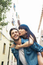 Happy loving couple happy young man piggybacking his girlfriend men while hug he Stock Photography