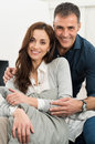 Happy loving couple portrait of sitting on couch looking at camera Royalty Free Stock Photos