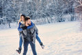 Happy loving couple walking in snowy winter forest, spending christmas vacation together. Outdoor seasonal activities. Royalty Free Stock Photo