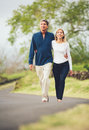 Happy loving middle aged couple walking on beautiful country road Royalty Free Stock Photography