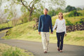 Happy loving middle aged couple walking on beautiful country road Stock Images