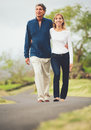 Happy loving middle aged couple walking on beautiful country road Royalty Free Stock Image