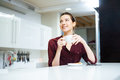 Happy lwoman drinking tea and smiling on the kitchen