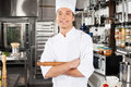 Happy male chef in kitchen portrait of young holding pin roll commercial Royalty Free Stock Photos