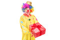 A happy male clown holding a red present Stock Photo