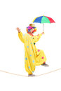 Happy male clown with umbrella walking on a rope Royalty Free Stock Photography