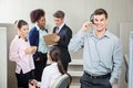 Happy male customer service representative using headphones with team discussing in background at call center Stock Photo