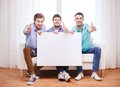 Happy male friends with blank white board friendship information and home concept showing thumbs up at home Stock Images
