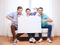 Happy male friends with blank white board at home friendship information and concept Royalty Free Stock Photography