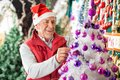 Happy male owner decorating christmas tree with balls at store Royalty Free Stock Photo