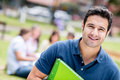 Happy male student holding a notebook and smiling Stock Photography