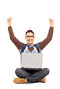 Happy male student sitting with a laptop and gesturing happiness Stock Images