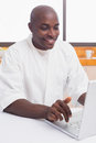 Happy man in bathrobe using laptop at table home the kitchen Stock Photo