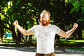 Happy man with beard is putting hands up as gesture of success Royalty Free Stock Photo