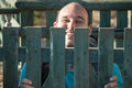 Happy man behind fence funny smiling wooden Stock Image