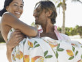 Happy man carrying woman on beach young men women during their honeymoon Stock Photo