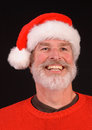 Happy man at christmas close up of a bearded in a santa hat and red sweater Stock Image