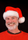 Happy man at christmas close up of a bearded in a santa hat and red sweater Stock Photography