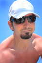 Happy man closeup of a bare chested smiling in the sunshine wearing a black goatee sun glasses and a white ball cap blue sky Royalty Free Stock Image