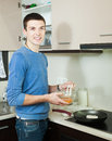 Happy man cooking frying squid rings in batter at kitchen Royalty Free Stock Images