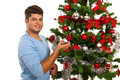 Happy man decorate christmas tree against white background Royalty Free Stock Photo