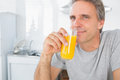 Happy man drinking orange juice in kitchen looking at camera Stock Photo