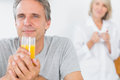 Happy man drinking orange juice in kitchen men with partner standing behind Stock Photos