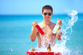 Happy man with drinks and water splash on the beach party Royalty Free Stock Photography