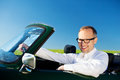 Happy man driving a convertible car over the blue sky background Royalty Free Stock Images