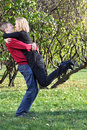 Happy man embraces and lifts woman in park