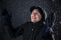 Happy man enjoys snow over black background Stock Images