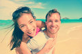 Happy man giving piggyback ride to woman at beach portrait of young men women excited couple are enjoying their summer vacation Royalty Free Stock Images