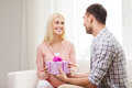 Happy man giving woman gift box at home Royalty Free Stock Photo