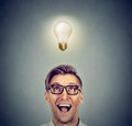 Happy man in glasses looking up at bright light idea bulb above head Royalty Free Stock Photo