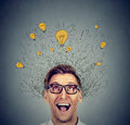 Happy man in glasses looking up with light idea bulb above head Royalty Free Stock Photo