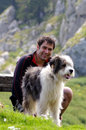 Happy man and his dog best friends portrait of a dark haired smiling pet a sheep in the middle of nature Royalty Free Stock Image