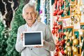 Happy man holding digital tablet in christmas portrait of senior while standing at store Stock Photography